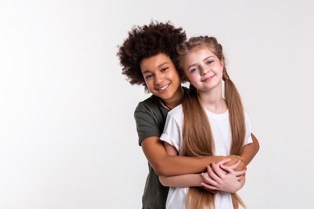 Junge, der sich fest umarmt. junge angenehme kinder, die schön zusammen aussehen, während sie die hände umarmen und verbinden connecting