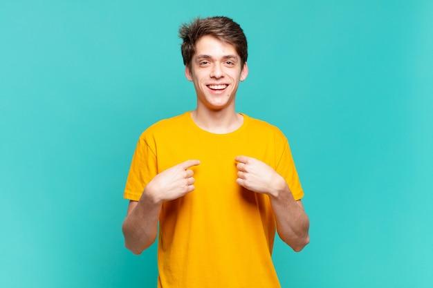 Junge, der sich glücklich, überrascht und stolz fühlt und mit einem aufgeregten, erstaunten blick auf sich selbst zeigt