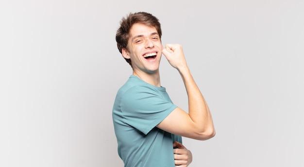 Junge, der sich glücklich, zufrieden und kraftvoll fühlt, fit und muskulös ist und nach dem fitnessstudio stark aussieht