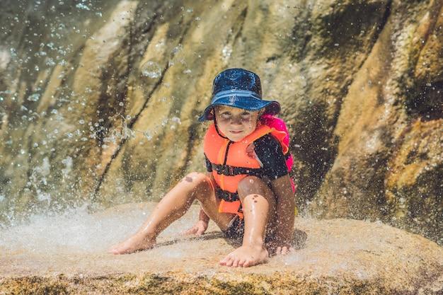 Junge, der sich unter einem wasserfall im aquapark entspannt. urlaubskonzept