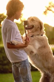Junge, der spaß mit hund im park hat
