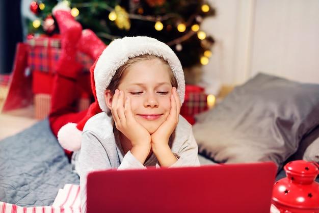 Junge, der spaß mit tragen feiertagsdekor unter verwendung der online-kommunikation durch laptop hat. entfernung weihnachtsfeier. soziale distanzierung