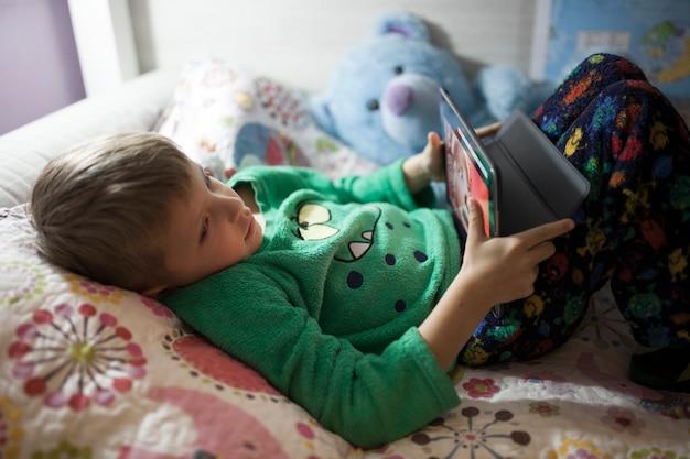 Junge, der spiele auf tablette spielt