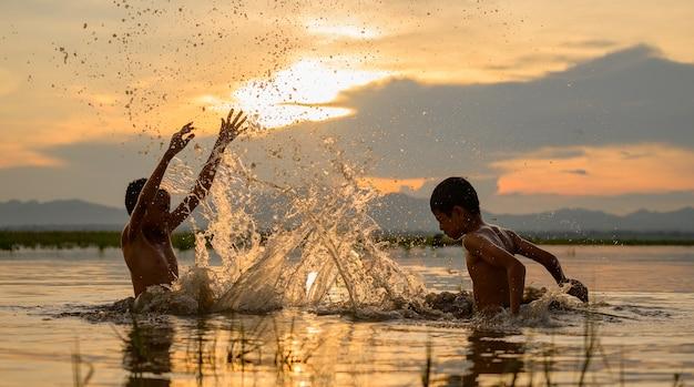 Junge, der spritzwasser im fluss während des sonnenuntergangs, spritzwasser, thailand spielt