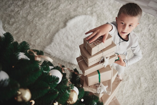 Junge, der stapel von weihnachtsgeschenken arrangiert