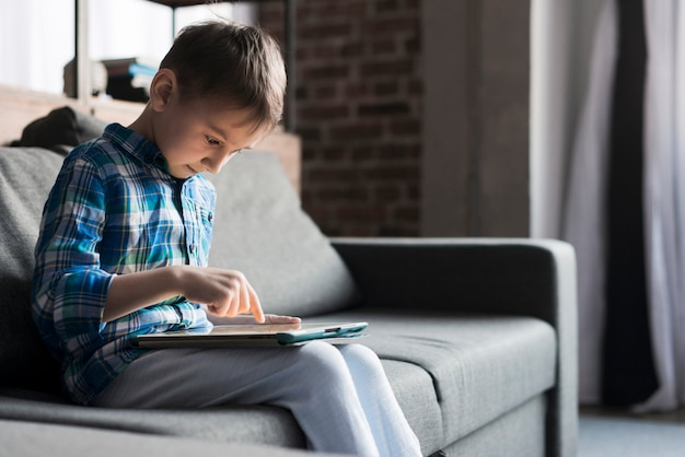 Junge, der tablette auf couch verwendet