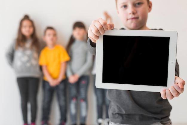 Junge, der tablette zeigt