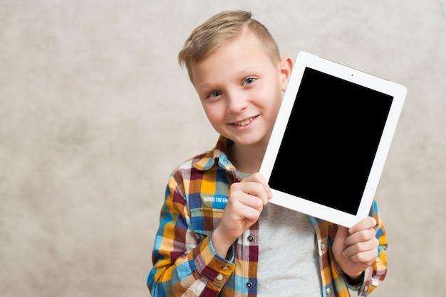 Junge, der tablettenschablone darstellt