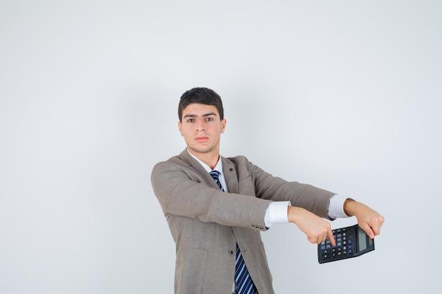 Junge, der taschenrechner hält, im formellen anzug darauf zeigt und ernst aussieht. vorderansicht.