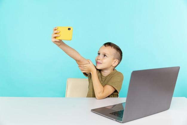 Junge, der telefon für videoverbindung benutzt, um seine hausaufgaben isoliert zu machen.