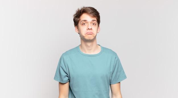 Junge, der traurig und gestresst ist, verärgert wegen einer bösen überraschung, mit einem negativen, ängstlichen blick