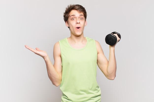 Junge, der überrascht und schockiert aussieht, mit heruntergefallenem kiefer, der ein objekt mit einer offenen hand an der seite hält. hantelkonzept