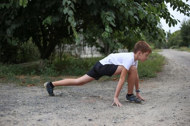 Junge, der übungen für beine im park ausdehnend tut