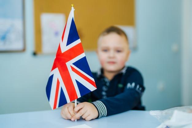 Junge, der union jack flagge hält. britische flagge in der vorderansicht. unscharfer hintergrund. nahansicht.
