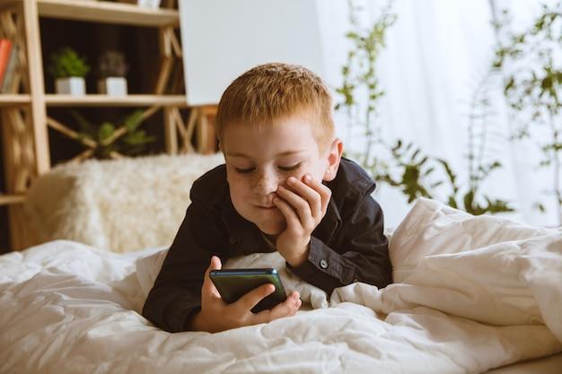 Junge, der verschiedene geräte zu hause benutzt. kleines modell mit smartwatches, smartphone oder tablet und kopfhörern. selfie machen, chatten, spielen, videos schauen. interaktion von kindern und modernen technologien.