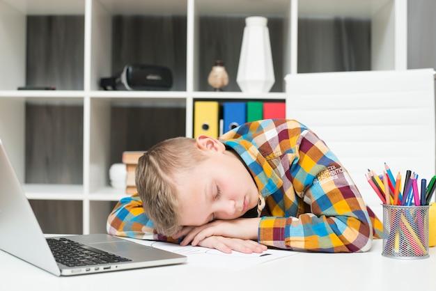 Junge, der vor laptop auf schreibtisch schläft