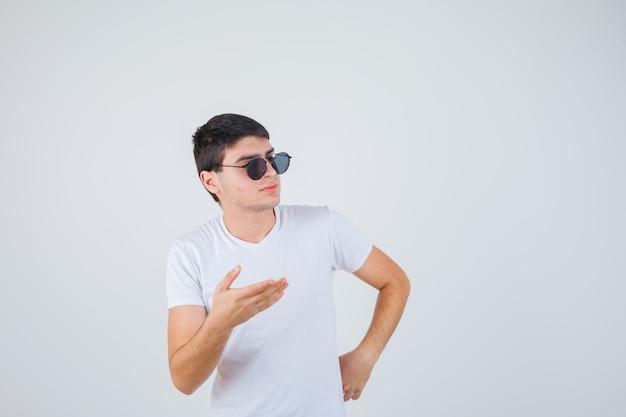 Junge, der vorgibt, etwas im t-shirt zu zeigen und selbstbewusst, vorderansicht aussehend.