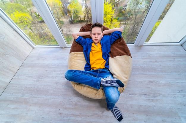Junge, der während der isolation auf dem balkon ruht. quarantäne für kinder zu hause. junge, der sich im weichen stuhl entspannt.