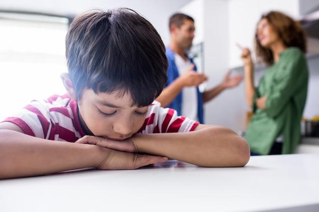 Junge, der während seine streitenen eltern traurig sich fühlt