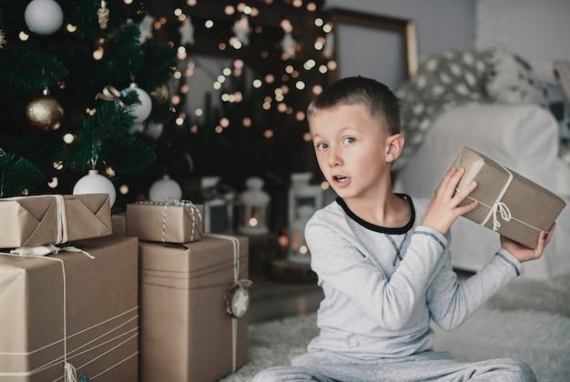 Junge, der weihnachtsgeschenke neben weihnachtsbaum arrangiert