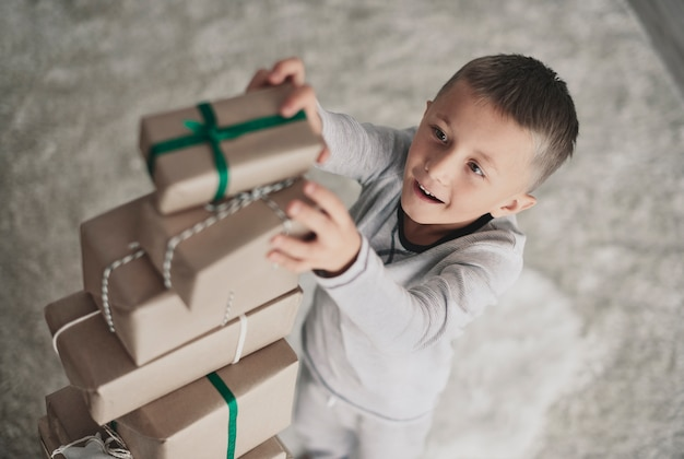 Junge, der weihnachtsgeschenke spielt und stapelt