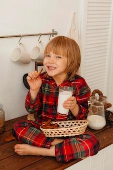 Junge, der weihnachtsplätzchen isst und milch trinkt