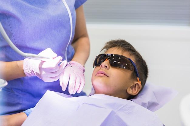 Junge, der zahnmedizinische überprüfung in der klinik hat