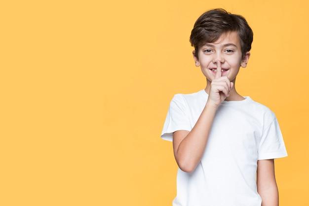 Junge, der zeichen für ruhe zeigt