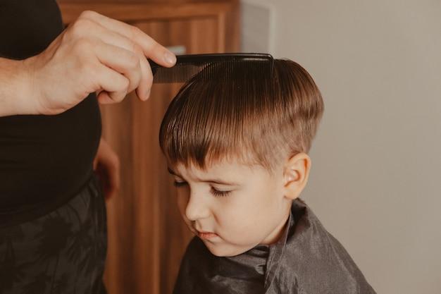 Junge, der zu hause einen haarschnitt bekommt