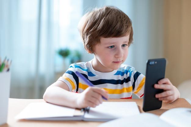 Junge, der zu hause mit smartphone studiert und schulhausaufgaben macht.