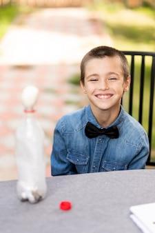 Junge, der zu hause physikalische experimente durchführt. eine erfahrung mit einem kind, wie man mit feuer ein gekochtes ei in den schmalen hals einer plastikflasche legt. hausgemachte kreativität mit einem kind
