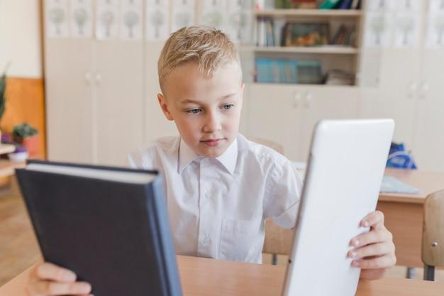 Junge, der zwischen buch und tablette an der lektion wählt