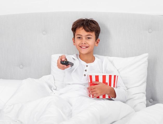 Junge des hohen winkels zu hause, der fernsieht und popcorn isst