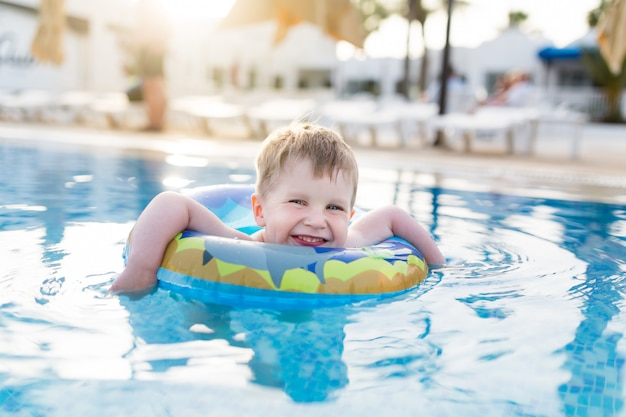 Junge des kleinen kindes, der in einem offenen pool schwimmt und spielt