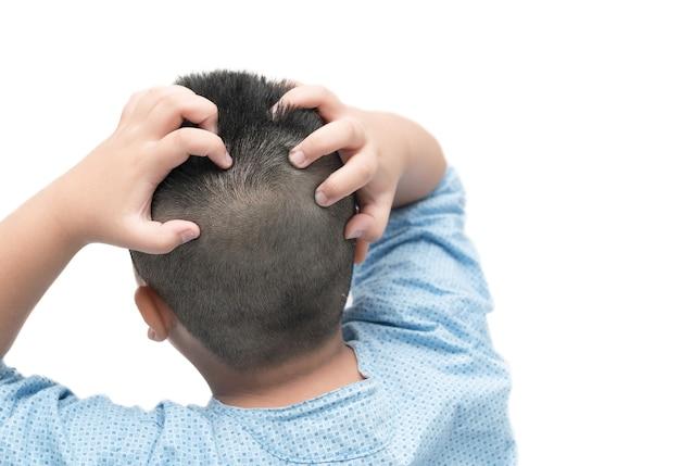 Junge des kurzen haares juckt sein haar auf getrenntem weißem hintergrund