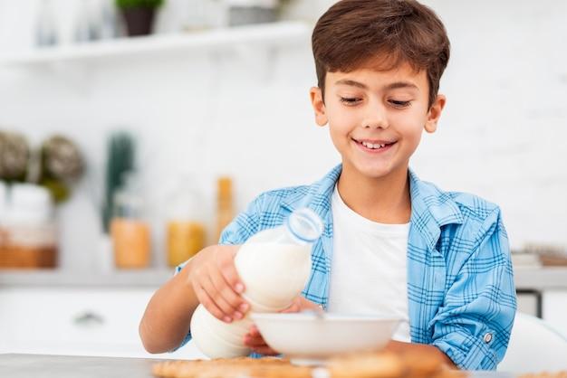 Junge des niedrigen winkels, der getreide mit milch zubereitet