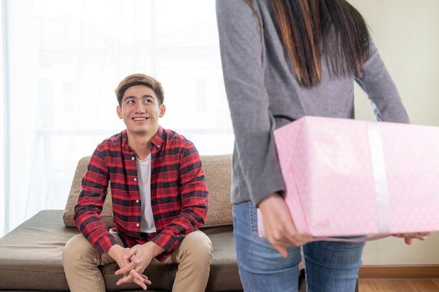 Junge des selektiven fokus, der auf couch mit dem fühlen aufregend bei der aufwartung des geschenkes von der hübschen frau sitzt