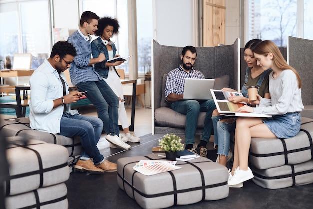 Junge designer arbeiten zusammen und sitzen auf gepolsterten hockern.