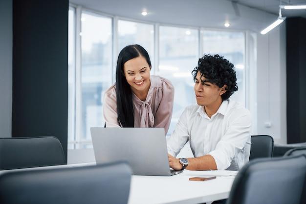 Junge designer. nette mitarbeiter in einem modernen büro lächelnd, wenn sie ihre arbeit unter verwendung des laptops erledigen