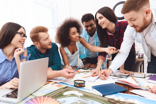 Junge designer verschiedener rassen diskutieren farben für das design
