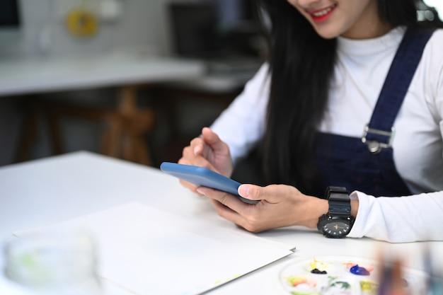 Junge designerin, die an ihrem arbeitsplatz sitzt und handy benutzt