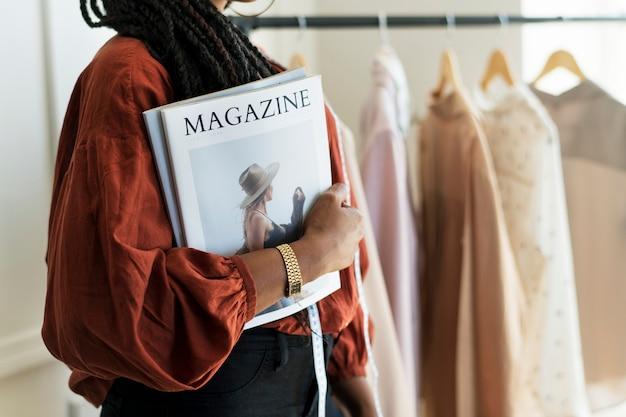 Junge designerin, die ein modemagazin hält