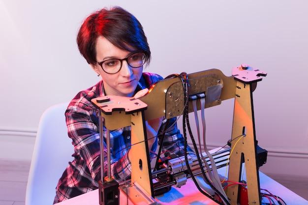 Junge designerin, die einen 3d-drucker im labor verwendet und ein produktprototyp-, technologie- und innovationskonzept untersucht.
