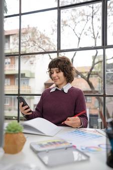 Junge designerin überprüft ihr smartphone