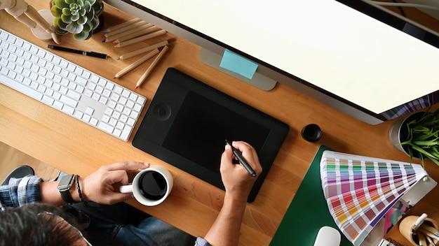 Junge designerzeichnungsskizzen auf digitaler grafischer tablette am studio. draufsicht geschossen