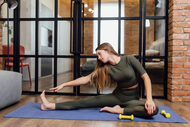 Junge diätologin und fitnessmodel, die zu hause mit hanteln auf einer matte kraft macht