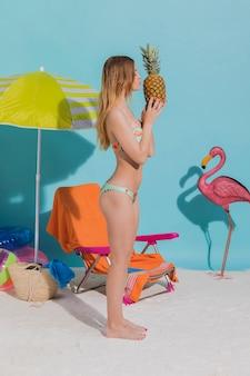 Junge, die auf sandfrau im bikini hält ananas stehen