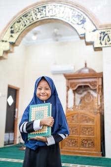 Junge, die den koran betend hält