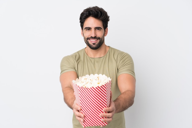 Junge, die eine große schüssel popcorn über lokalisierter wand halten