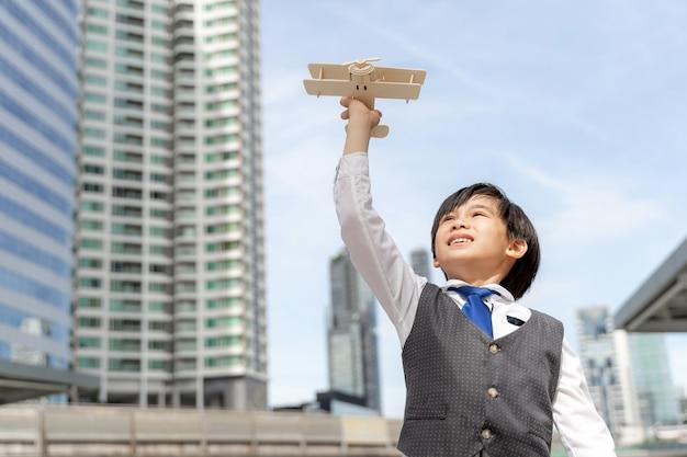 Junge, die fliegerspielzeugflugzeugphantasie spielt, die davon träumt, eine pilotzukunft auf geschäftsviertel urban zu sein